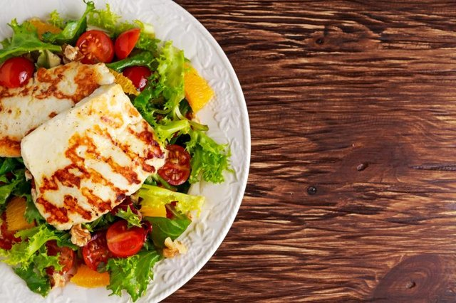 A vegetarian lunch of grilled Halloumi Cheese salad with orange, tomatoes and lettuce.