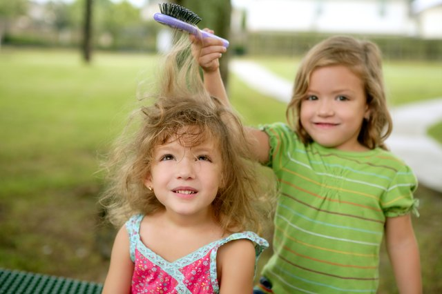 toddler having her hair brushed by sister