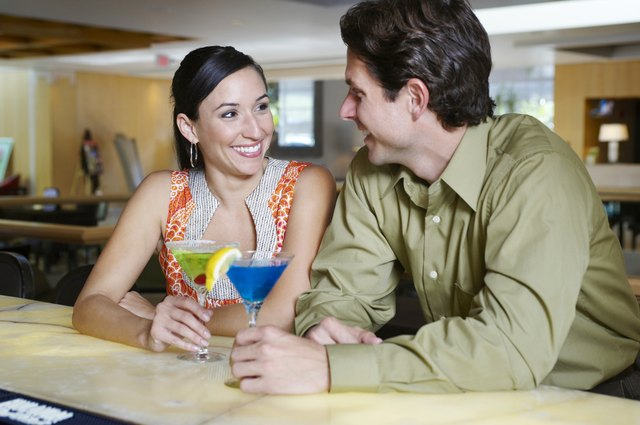 Two people have a cocktail together at the bar.