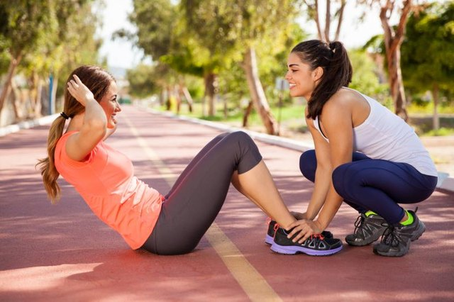 Young female friends helping each other to do some crunches before going for a run at a running track