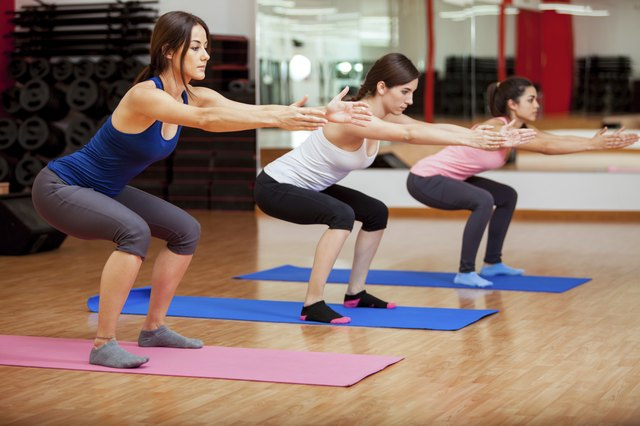 Three women do squats at the gym.