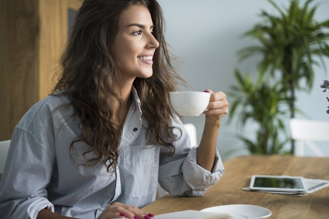 Woman drinking cup of coffee with Truvia.