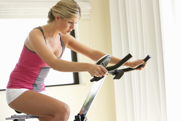 woman using an exercise bicycle at home