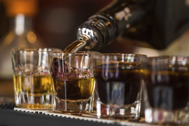 Close-up of whiskey shots being poured