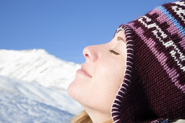 Woman breathing in fresh mountain air during the winter