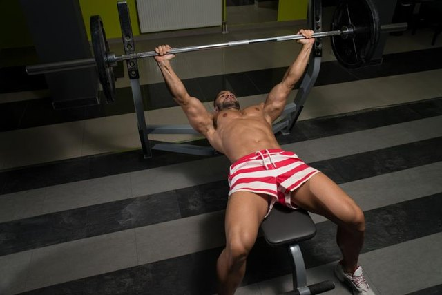 Do a decline bench press on specialized equipment.