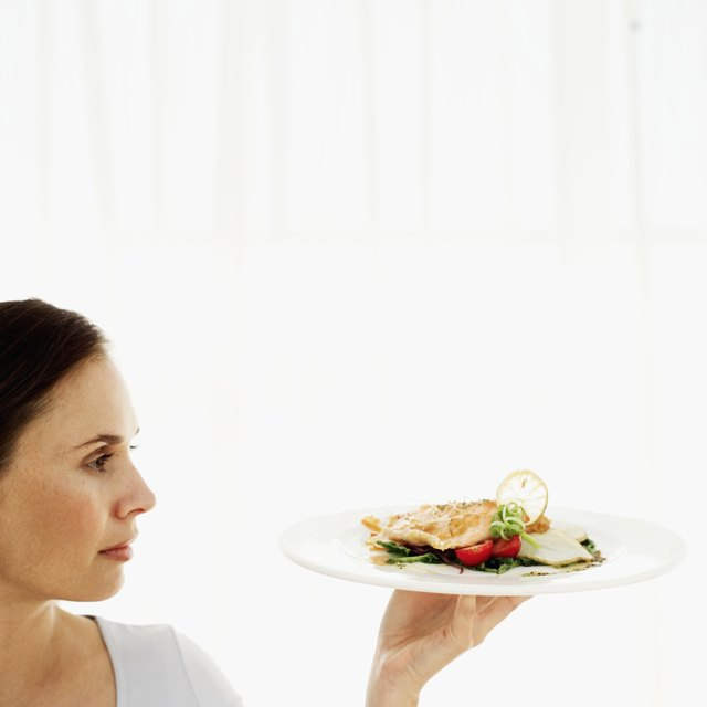 Young woman holding up a plate of salmon and vegetables.
