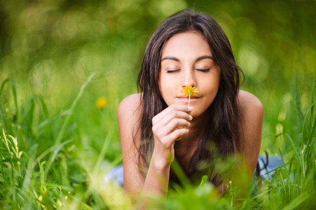Young woman smelling a wildflower