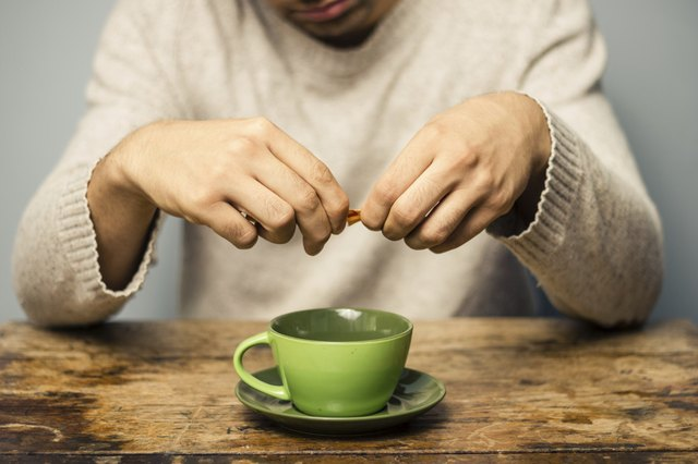 Man pours Truvia in his cup of coffee.