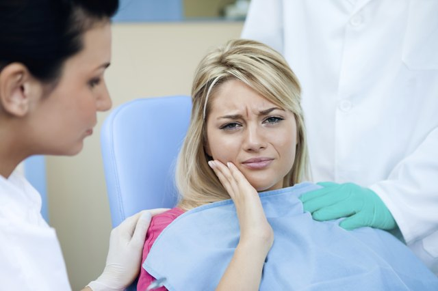 A woman being consoled at the dentist's office.