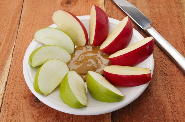 Sliced apples with spoonful of peanut butter