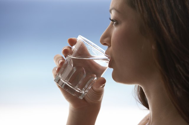 A woman drinks a glass of water.