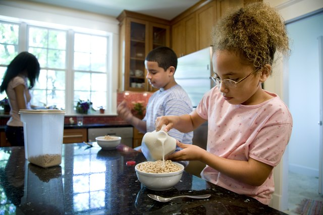 Girl pouring milk on cereal