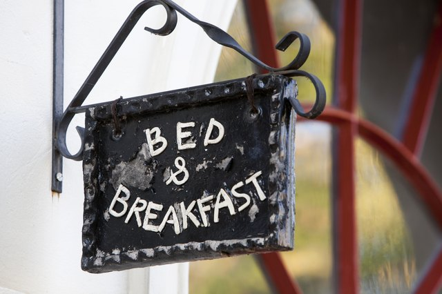 A close-up of a hand-made bed and breakfast sign.