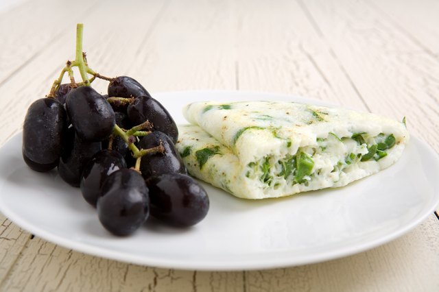 An egg white omelette with spinach on a plate with purple grapes.