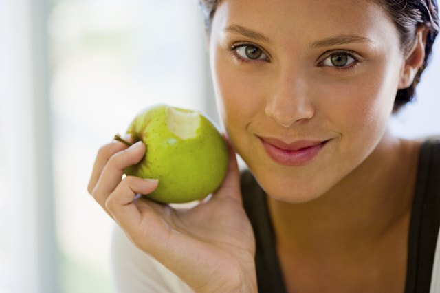 Woman holding an apple after biting it