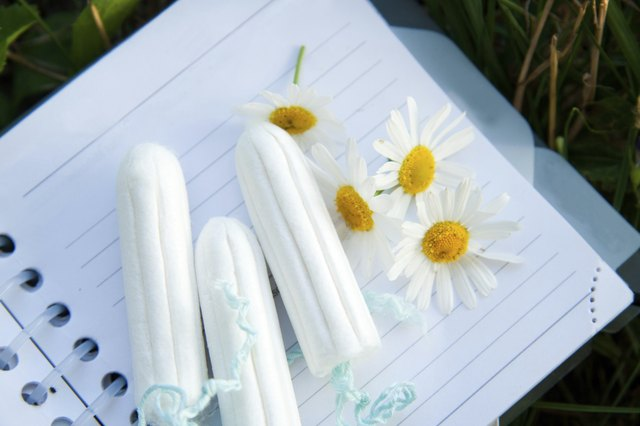 A schedule book with feminine care products and flowers on it.