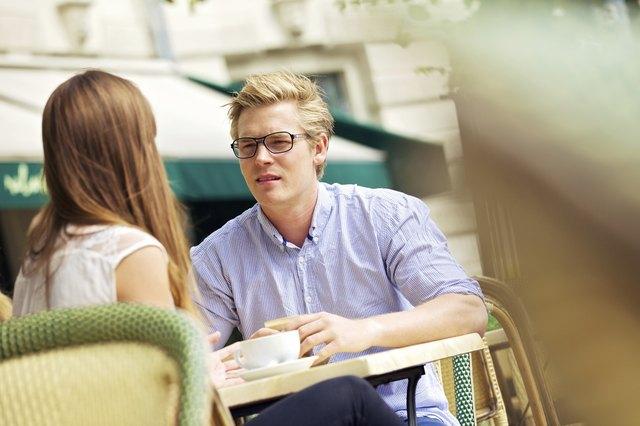 A couple has a serious conversation at a cafe.