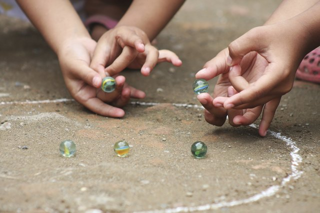 Two children playing marbles
