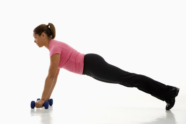 Placing your hands on weights during a push-up lessens the bend in the wrist joint.