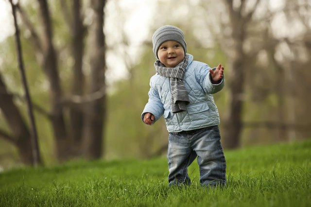 A baby walks in the grassy park.