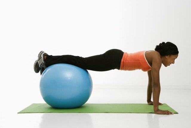 Begin a pike by getting into a push-up position using a stability ball.