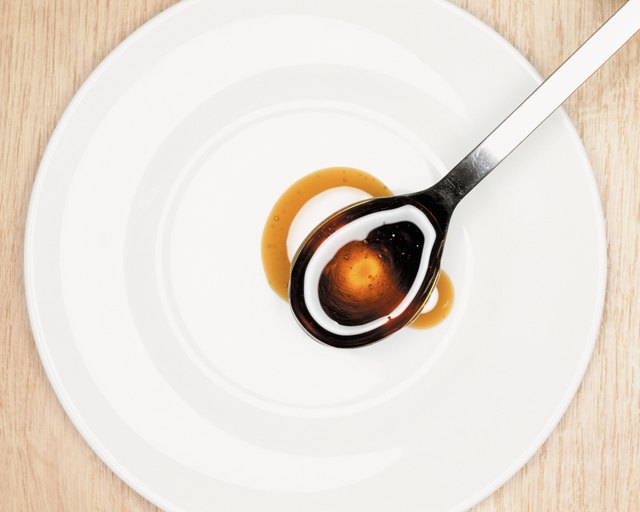 A spoonful of molasses over a plate.