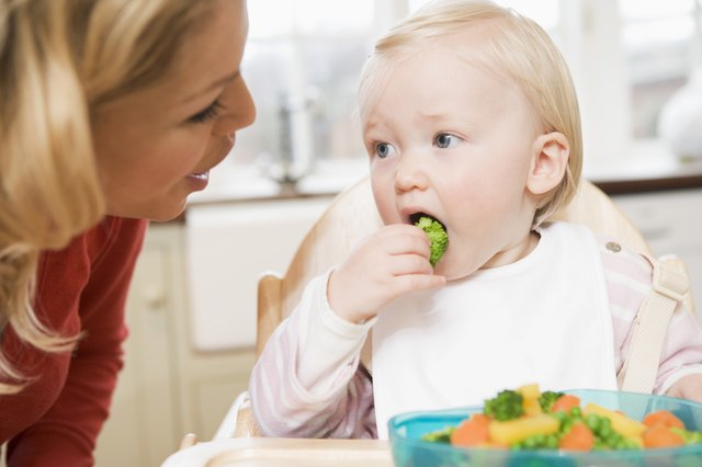 A mother encourages her toddler to eat a piece of broccoli.