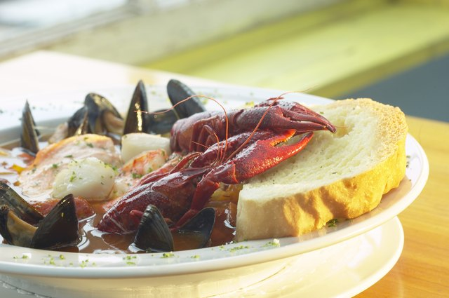 A bowl of lobster, shrimp, scallops, and mussels in broth with a slice of bread.