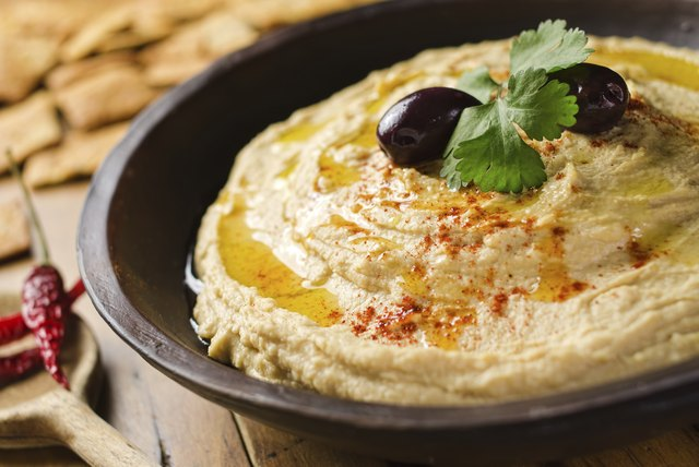 Hummus with herbs, olive oil and olives