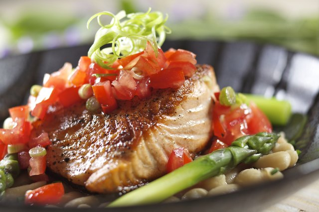 A salmon entree accompanied with fresh tomato sauce, asparagus, and white beans.