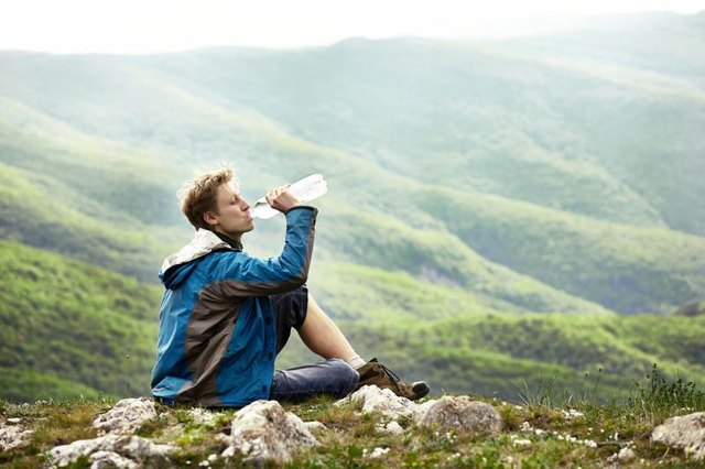 Man on the edge of the hill in Carpathian Mountains drinking alkaline water.