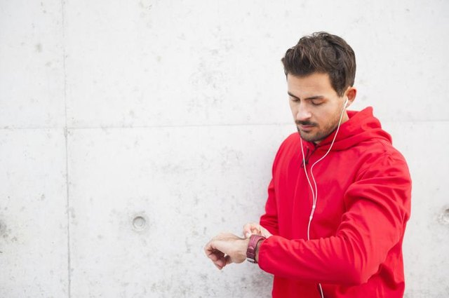 Male runner checks his fitness wearable to get stats on his performance