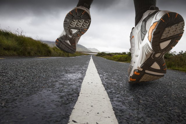 A close-up of a runner using the forefoot on a paved road.