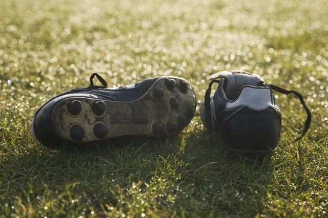 A pair of soccer shoes with cleats on a field.