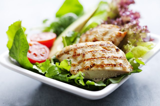 Grilled chicken served on top of a green salad.