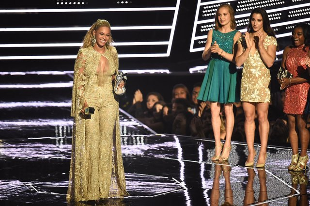 Beyoncé accepts the female video award as the Olympic champions look on.