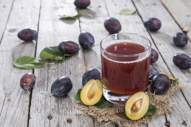 A glass of prune juice on a wood table with fresh plums.