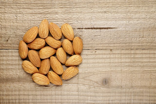 A handful of almonds on a wooden surface.