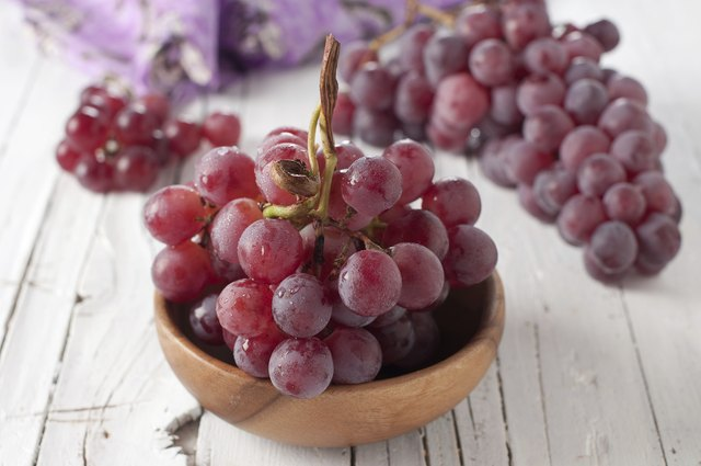 A small bunch of red grapes in a wooden dish.