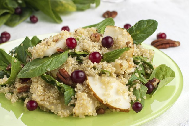A quinoa salad with spinach, pears, grapes, and pecans.