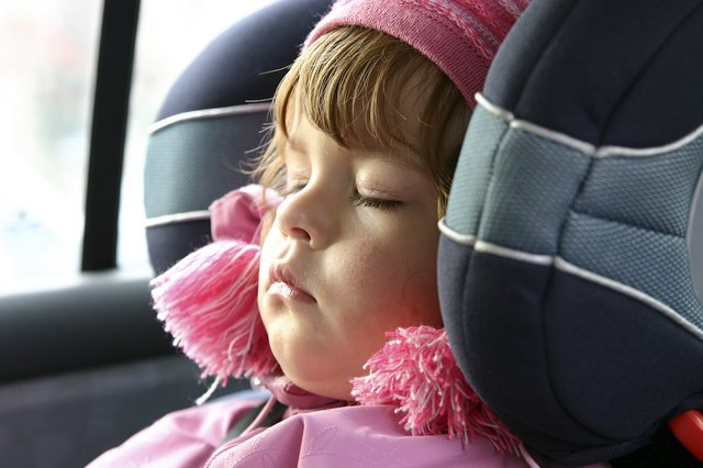 A toddler sleeps with her head propped up in the booster head rest.