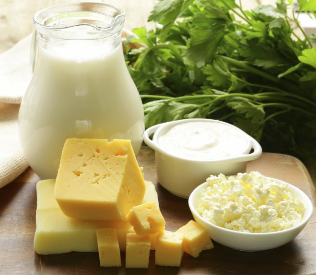 Dairy products on a cutting board with fresh herbs.
