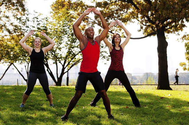 Outdoor fitness class performs jumping jacks