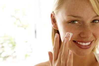 Young smiling woman applying moisturizer to her face.