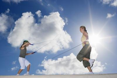 Mother and daughter jumping rope outdoors.
