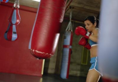 Young female boxer punching heavy bag.