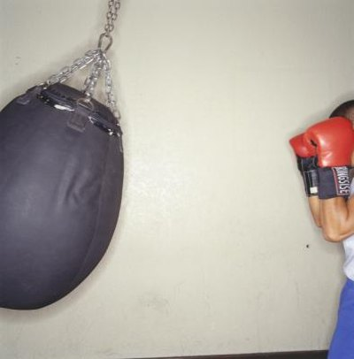 Woman with boxing gloves on punching bag.