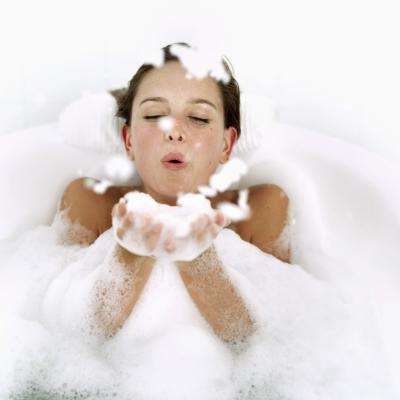 Aerial view of a young woman in a bubble bath blowing bubbles.