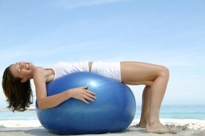 Woman on exercise ball stretching.